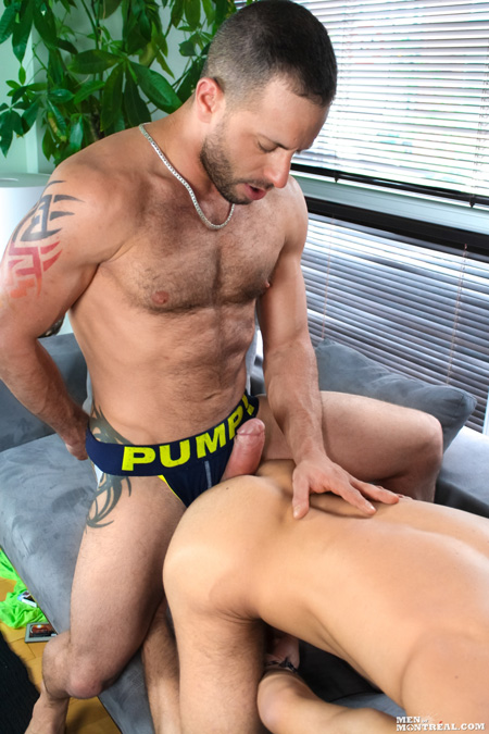 Tattooed hairy hunk in a jockstrap with his huge erection sticking out.