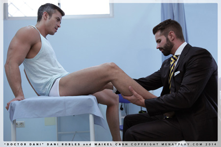 Doctor in a suit and tie examining a muscular male athlete.