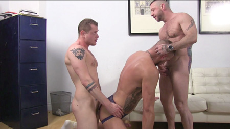 Three heavily tattooed men having gay bareback sex.