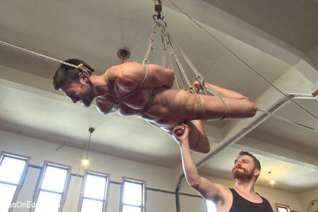Hairy chested male suspended from the ceiling with rope while his dick is milked by another man.