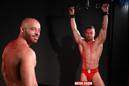 Muscular man in red jockstrap strung up and waiting to get fucked bareback by his bald, bearded boyfriend.