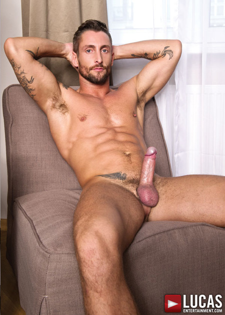 Fit, tattooed guy naked with his thick uncut cock erect.