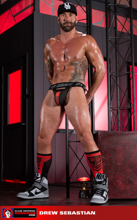 Tattooed muscle hunk oiled up in a jockstrap and athletic socks.