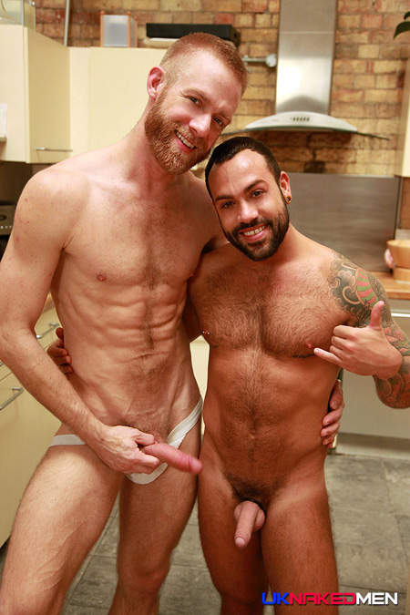 Tall, thin redheaded male with a red beard pulls his dick out of his jockstrap while he poses next to an uncut beefy bear.