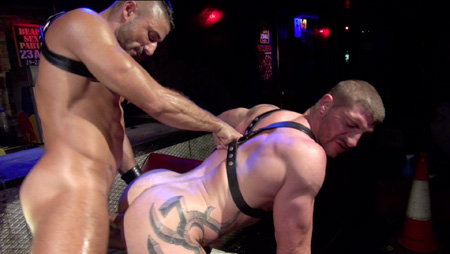 Tall, beefy, tattooed man in a leather harness getting fucked doggy-style.