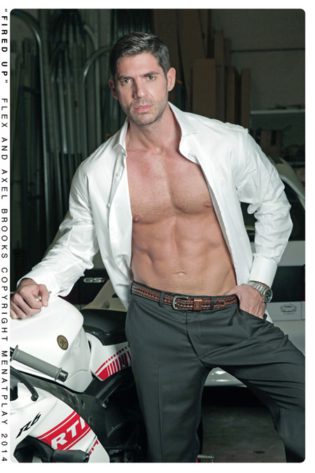 Muscular silver fox in a suit with his button down shirt open revealing his chest.