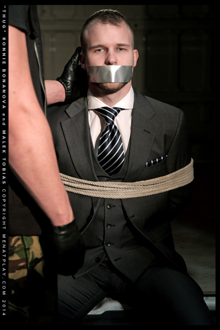 Blue-eyed businessman in a suit tied up with rope and his mouth closed shut with duct tape.
