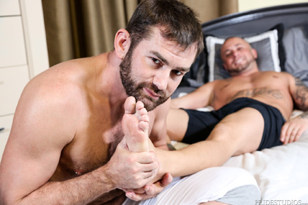 Stocky bearded guy rubbing another man's bare feet.