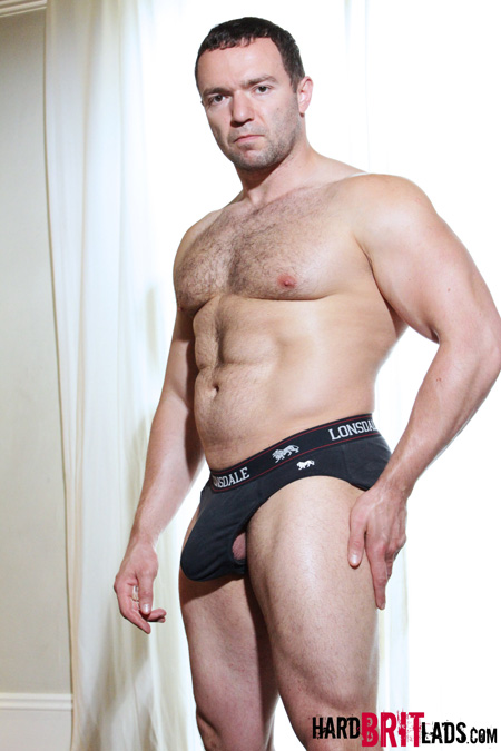 Stocky muscular rugby player with an erection in his tight black underwear.