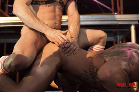 Beefy muscle stud in a leather harness and OTC athletic socks fucking another guy in the ass face down on the floor of a leather bar.