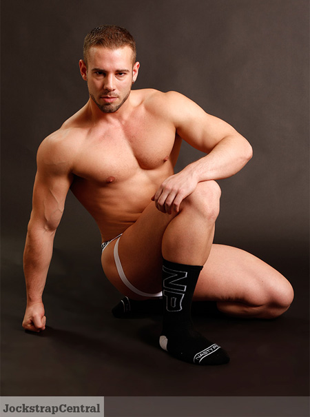 Smooth muscle stud in nothing but a Nasty Pig jockstrap and athletic socks.