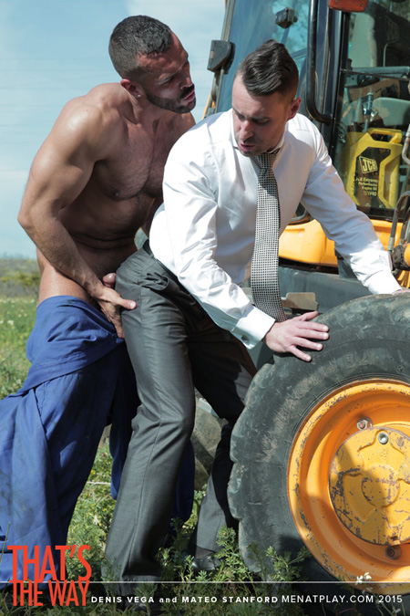 Muscular farmer grabs a handful of a businessman's round bubble butt in his suit pants.