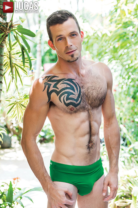 Gorgeous young hairy muscle stud with chest tattoo in a green Speedo swim brief.