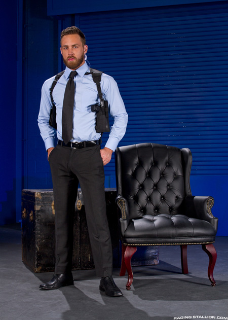 Bearded, muscular private security guard in a tight suit with a shoulder holster.