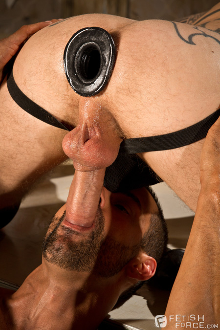 Muscle stud with a funnel in his ass getting his huge cock sucked by a bearded man.