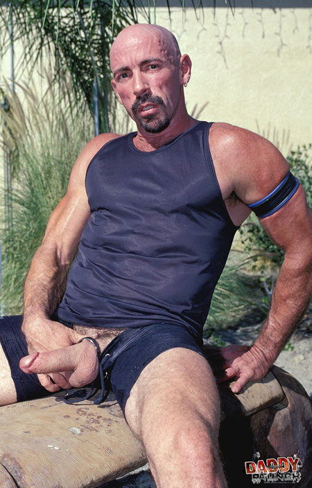 Hung Daddy in athletic wear exposing himself on a rock.
