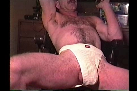 Hairy Daddy in a jockstrap with his balls hanging out.