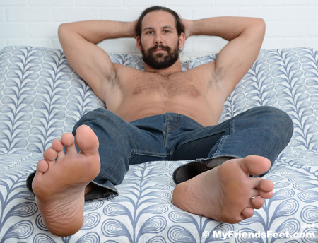 Furry muscle guy in jeans with bare feet.