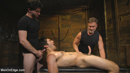 Older and younger leathermen edge a hunky stud who they have tied up in bondage.