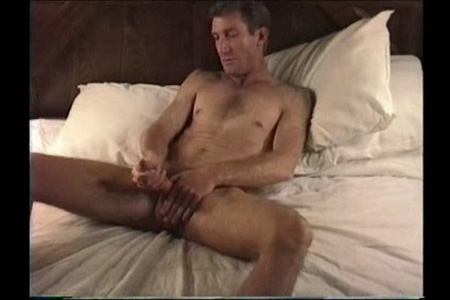 Mature straight guy masturbating in bed.