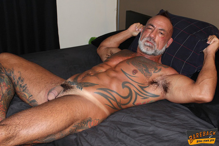 White beard muscle Daddy in the nude showing off his tattoos and male bikini tan lines.