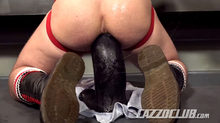 Guy with a bubble butt in a jockstrap and boots squatting on an enormously huge dildo.