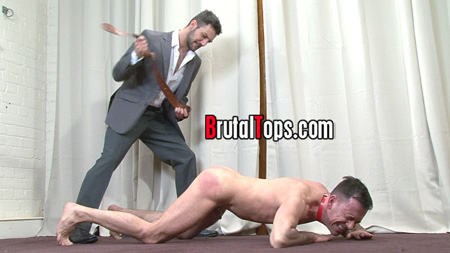 Man in a suit beating a naked man with a belt.