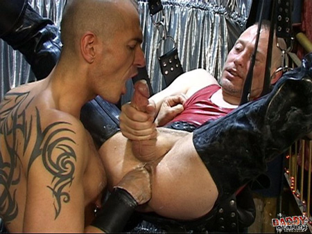 Inked up leathermen fist each other in their skinhead gear and a leather sling.