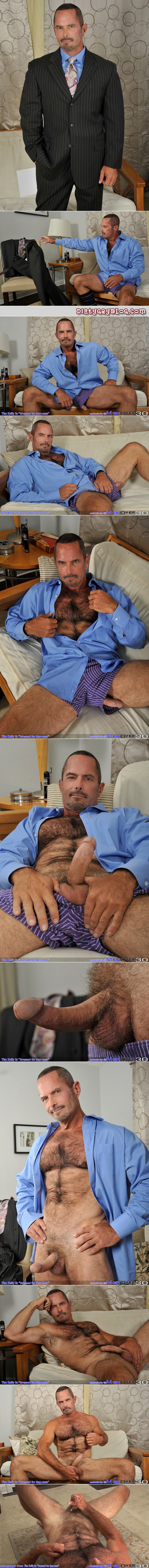 Hairy older man in a suit with his cock hanging out of his boxer shorts jerking off shoots a load of cum on his furry stomach.