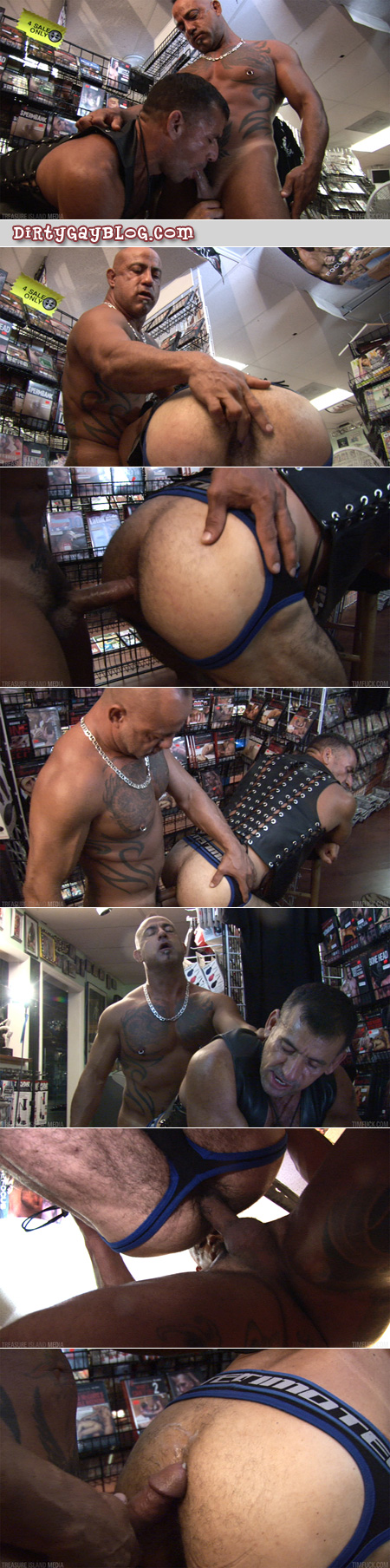 Hairy daddies fuck bareback in the aisle of an adult video store.