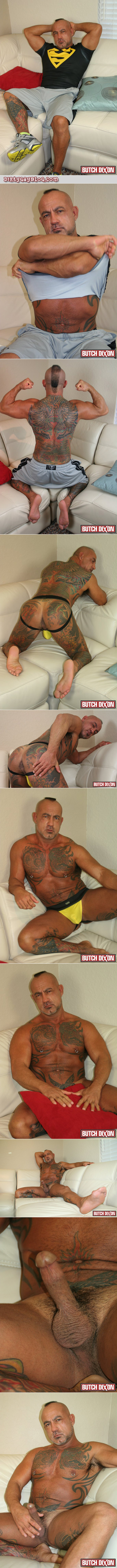 Tanned, beefy, heavily tattooed older man in a jockstrap jacking off on the couch.
