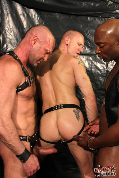 German cum pig in a leather jockstrap being inspected by two additional leathermen.