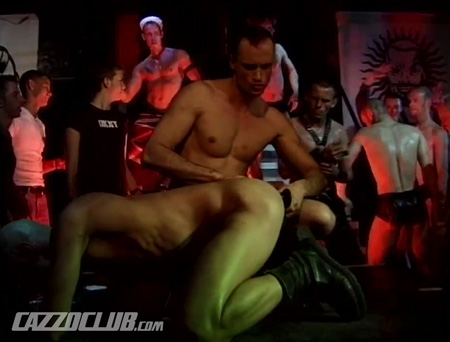 A guy on all fours getting penetrated with a dildo in front of a dance club full of gay men.