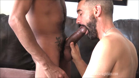 Bearded male trying to put an enormous Latino penis in his mouth.