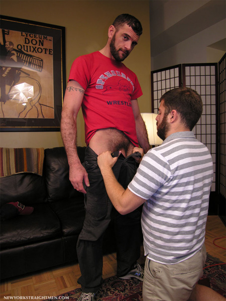 Hairy straight guy with a thick beard about to receive a blowjob from another guy.