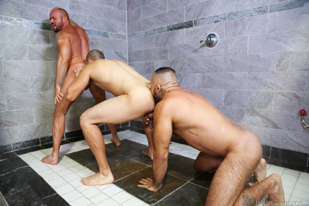 Daisy chain of men eating ass in a large open shower.