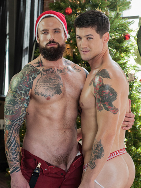 Tattooed muscle Santa posing shirtless with a smooth inked bottom he's about to fuck.