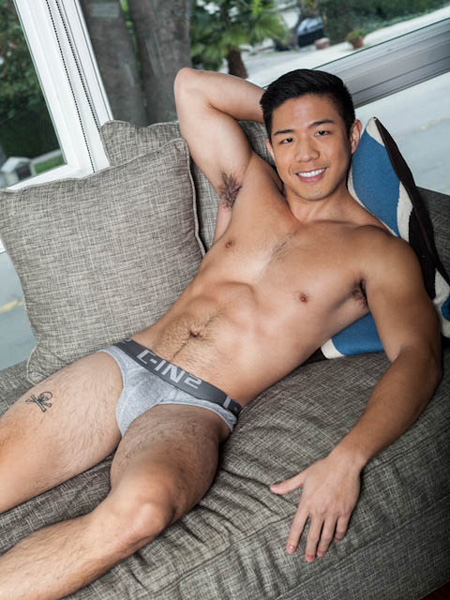 Hairy, muscular Asian man lying on the couch in tight grey briefs.