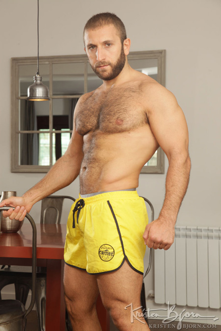 Hairy muscular Arab guy in running shorts with his hairy chest exposed.