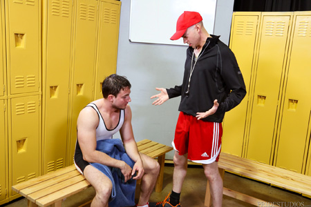 Muscular male wrestlers eyes the penis outline his coach is showing in his athletic shorts.