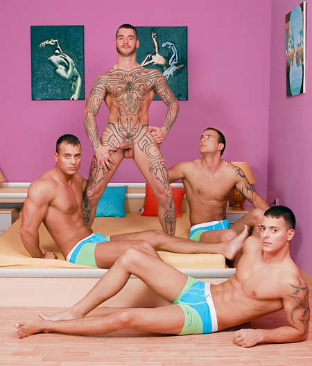 Heavily tattooed gay hunk naked with gay male triplets.