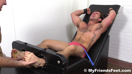 Hairy muscle stud bound and having his feet tickled by another man.