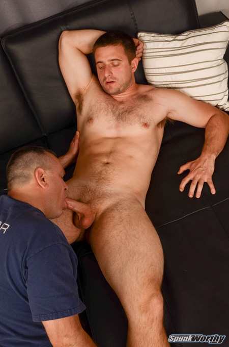 Beefy straight guy receiving a blowjob from another man.