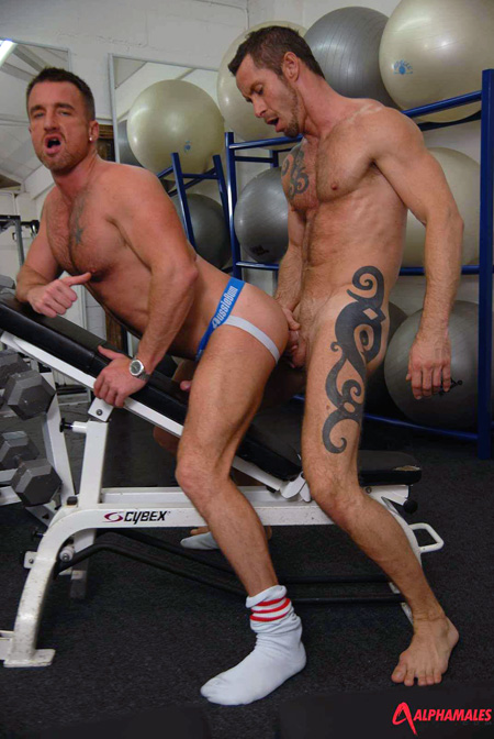 Tattooed muscle stud fucking Ross Hurston in the ass through his open back jockstrap.