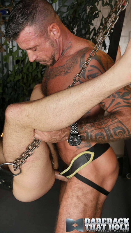 Tattoo muscle Daddy in a leather zip-front jockstrap fucking a guy bareback in a leather sling.