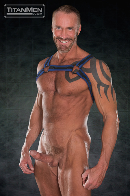 Tattooed silver fox in a leather harness showing off his rock hard erection.