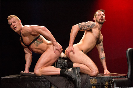 Muscle men sharing a big double-headed dildo.