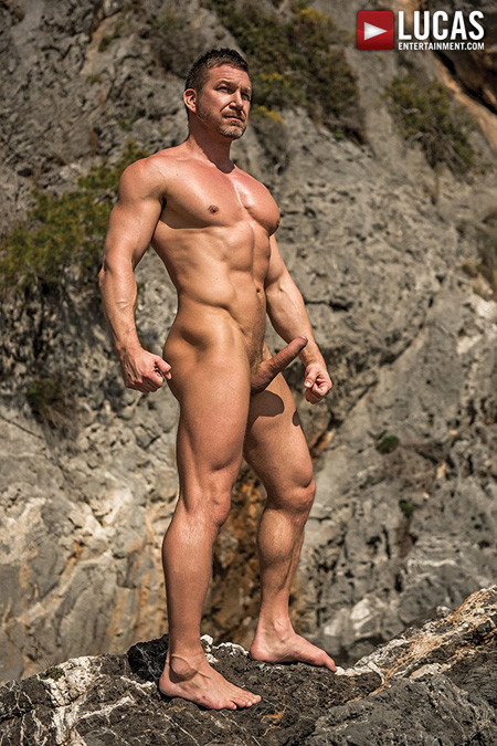 Muscle Daddy Tomas Brand nude and with an erection at the beach.