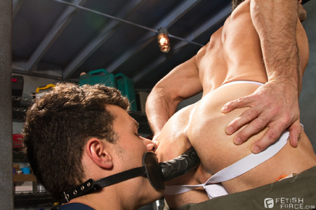 Mechanic in a jockstrap sits on a dildo held in the mouth of another man.