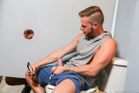Hunky blonde masturbating on his phone at a gloryhole.